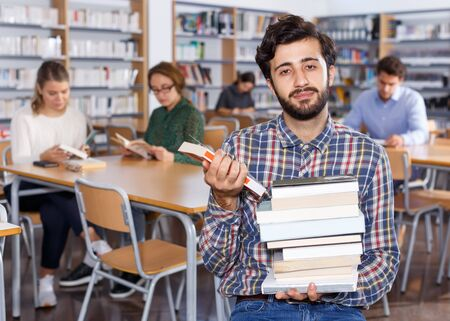 Portrait of glad bearded man sitting in public library with stack of books in hands Stock Photo