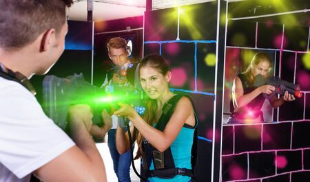 Two emotional happy cheerful smiling players standing opposite each other with laser pistols in laser tag room