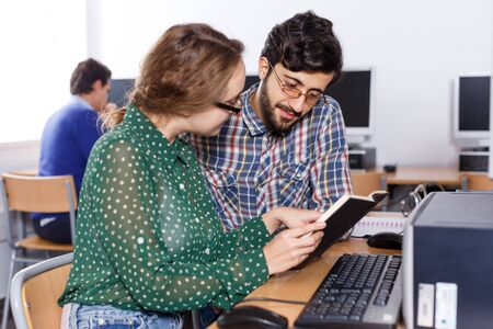 Intelligent female and male students working together with computer and book in university library