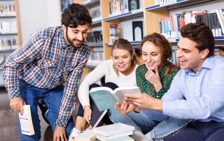Group of happy positive smiling students studying together in library, sitting on floor on background with bookshelves Foto de archivo