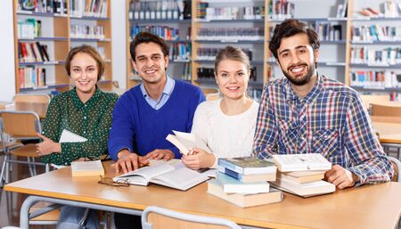Group portrait of cheerful positive young adults engaged in research, working together in public library