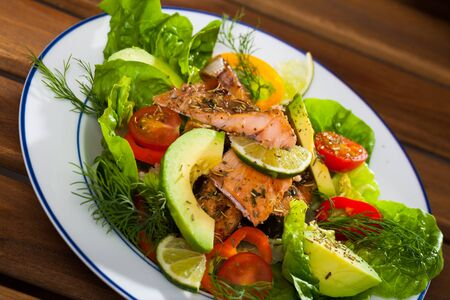 Appetizing fish salad with tender roasted trout fillet, avocado, cherry tomatoes and greens Foto de archivo