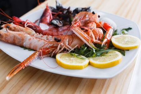 White plate with cooked shrimps, langoustines, clams with herb and lemon slices on wooden background