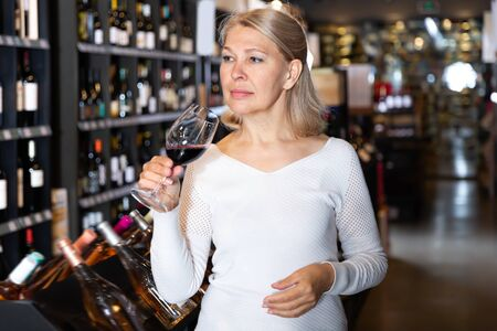 Middle aged woman inspecting quality of red wine in wine store in search of perfect wine for solemn occasion