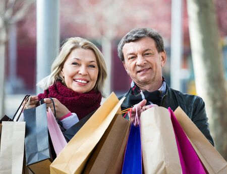 Cheerful smiling positive mature spouses with shopping bags in spring day