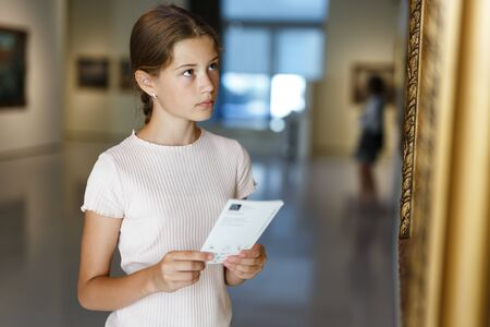 Attentive teenage girl exploring artworks in modern museum