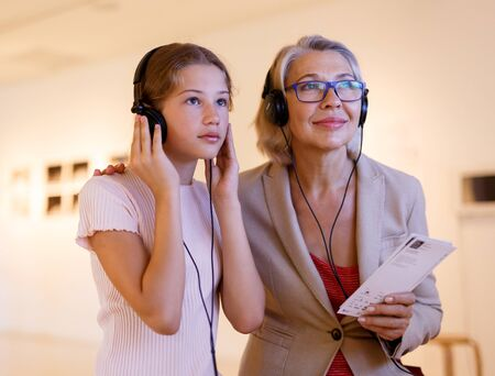 Attentive tween girl with senior woman exploring art museum on self-guided tour