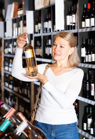 Attentive middle aged woman looking for perfect wine for solemn occasion in wine store