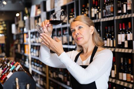 Focused mature woman wine producer inspecting quality of wine in wineshop on background with shelves of wine bottles