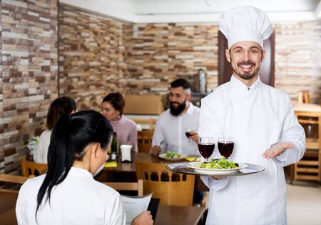 Cheerful chef taking care of adults at cafe table