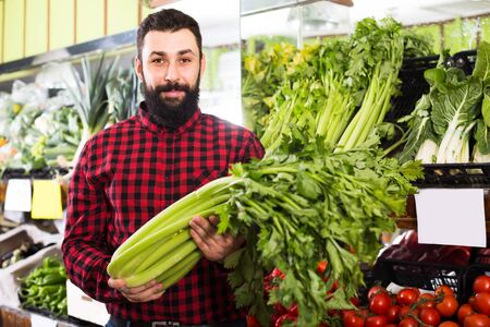 Adult male seller offering celery in grocery shop