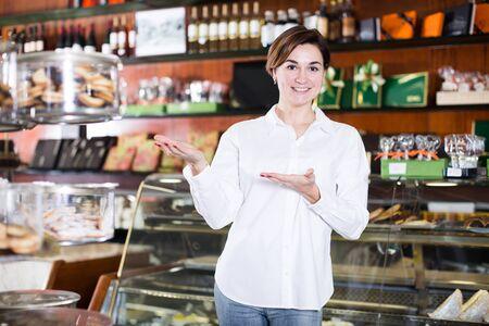 Vendeur de jeune femme affichant l'assortiment de confiserie