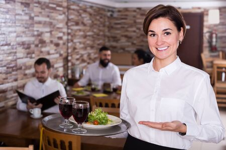 Smiling waitress bringing order for guests in traditional cafe