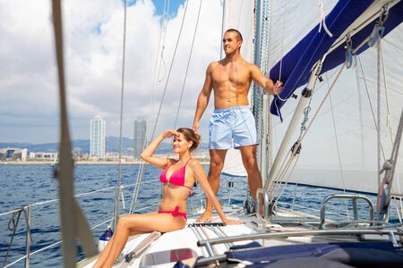 Young loving positive smiling couple enjoying sea trip on pleasure sailboat along coast of Barcelona on sunny summer day