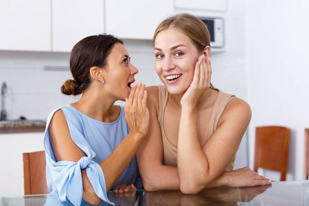 Portrait of young smiling girlfriends sharing secrets and chatting at table at home