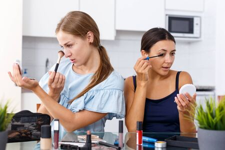 Two young women friends talking and applying make up in kitchen 版權商用圖片