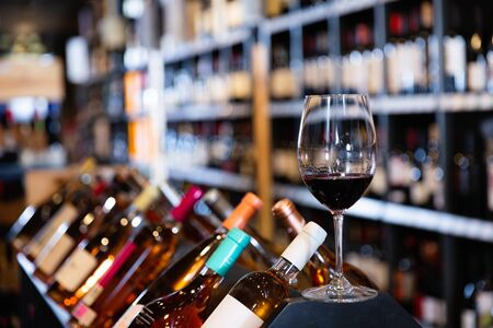 Closeup of tasty cool red wine glass on blurred background with shelves in wine shop Banco de Imagens