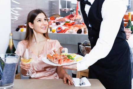 Polite waiter serving ordered seafood dishes to attractive cheerful positive girl at fish restaurant