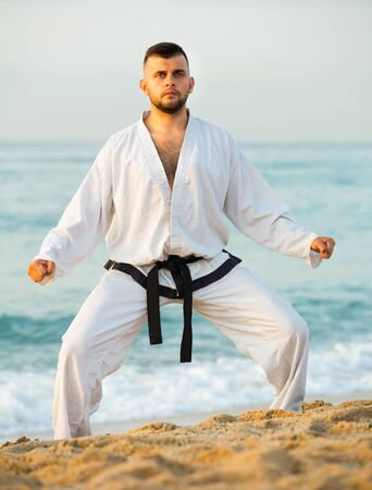 Adult man is exercising to doing the Shiko-dachi stance on the beach near the sea. 免版税图像