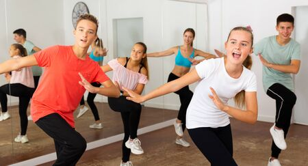 Teenage dancers practicing active vigorous dance in modern studio