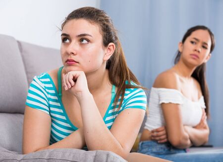 Two quarreled girls teenagers ignoring each other on sofa at home