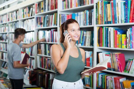 Smiling teenager girl holding open book and talking on mobile phone in store