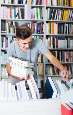portrait of teenage boy standing among bookshelves and searching for book in library