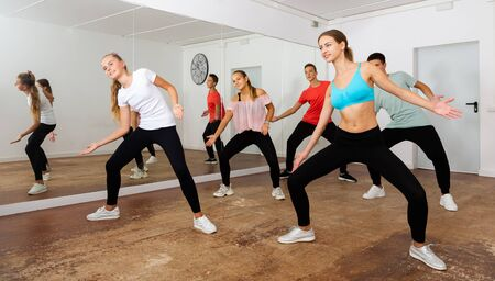 Group of teenagers participating in dance class, following their young female teacher in dance school