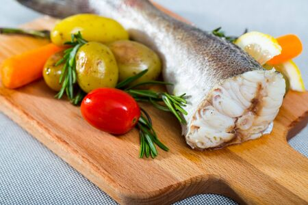 Hake baked by rustically style. Hake 250 gramm (it is better to take the tail), rub it with salt and pepper, bake in the oven for 20 minutes at 220 gramm Served with potatoes and fresh vegetables Stockfoto