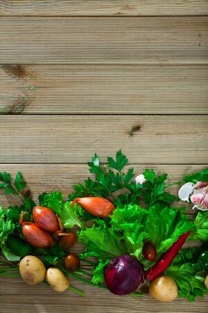 Ingredients for vegetarian dishes. Fresh raw vegetables, herbs and seasonings on wooden surface