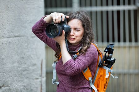 Cheerful glad happy woman taking picture with camera outdoors in town Foto de archivo