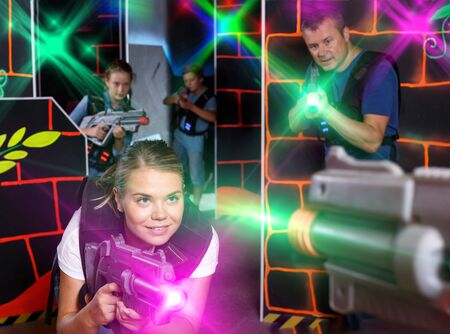 Smiling young female aiming laser gun at other players during laser tag game indoors