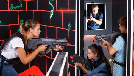 Group of happy kids and adults with laser pistols having fun on lasertag room