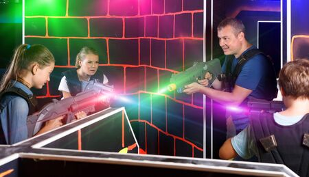 young parents and children with laser pistols playing laser tag in dark labyrinth