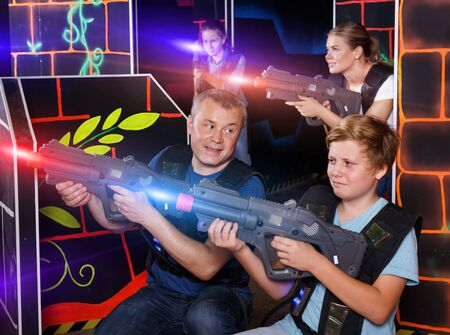 Modern young father and teen son with a laser pistols playing laser tag in dark labyrinth