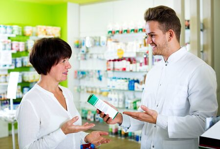 Smiling adult man druggist in white coat giving advice to customers in pharmacy