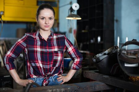 Young brunette master is posing with tools in workshop. Banque d'images