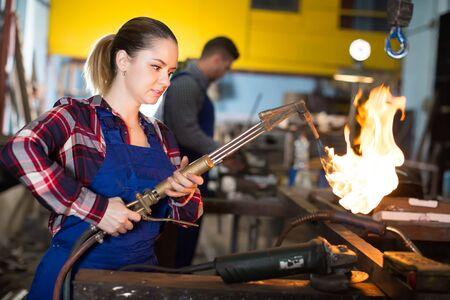 femalel worker is standing with burner in workshop.