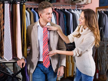 Young pleasant smiling couple choosing new tie in men's cloths store