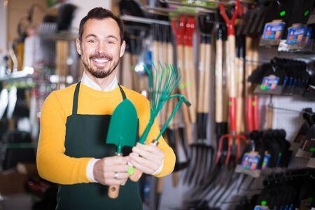 male seller showing assortment оf equipment in garden equipment shop