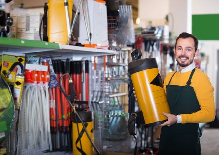 professional male seller showing assortment оf equipment in garden equipment shop