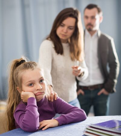 Young parents lecturing their daughter for bad behavior at home Stock Photo