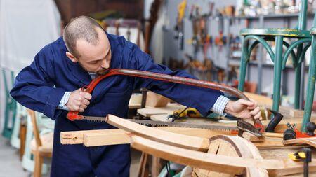 Professional carpenter engaged in restoring antique furniture using instruments