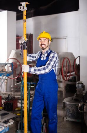 happy working man practicing his skills erect trestle at workshop