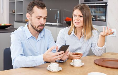 Young discontented couple sitting with phones in kitchen interior, finding out relationship