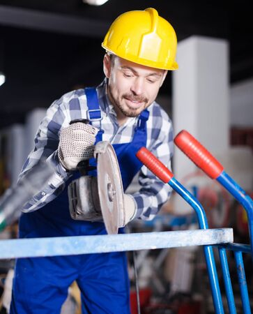 Male worker starting to assemble with scaffoldings at workshop