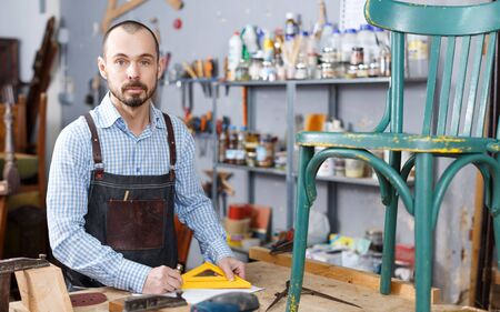 Craftsman looking at drawing in process of restoration vintage chair in workshop