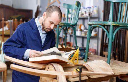 Portrait of skilled male artisan with book working at vintage furniture repair workshop