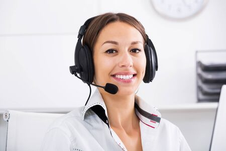 Portret of positive brunette woman talking with customer using hands-free set at call center Standard-Bild