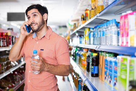 Happy cheerful positive man is choosing water with help mobile in supermarket.
